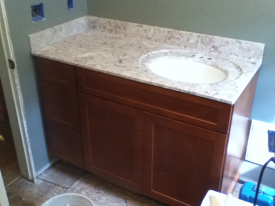 Bathroom vanity installation with marble counter top and back splash.