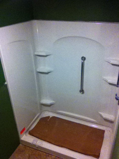 Walk-in shower stall installed with moisture resistant drywall surrounding the shower unit.