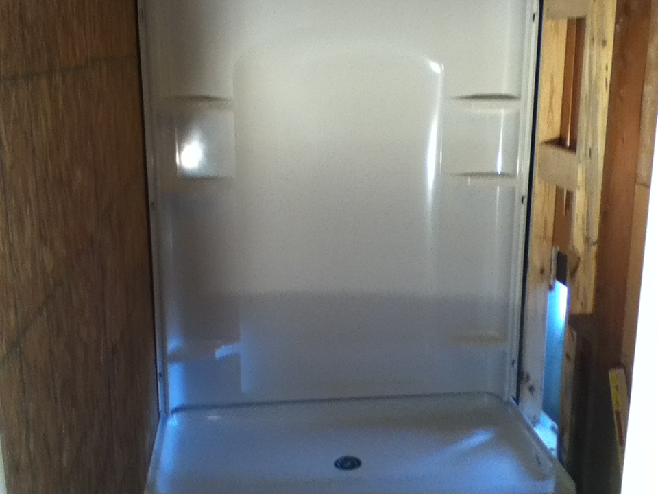Walk-in shower stall during installation. Shower base and back wall unit currently installed.
