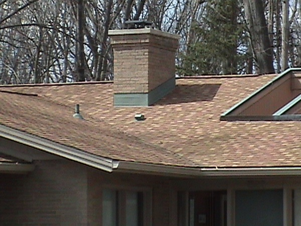Detail of the flashing around the chimney on this homes shingled roof replacement.