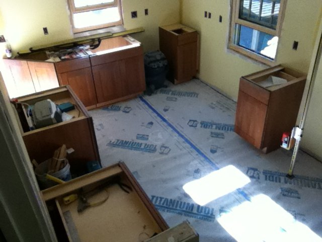 Kitchen base cabinets installed, flooring installed and protected during construction.