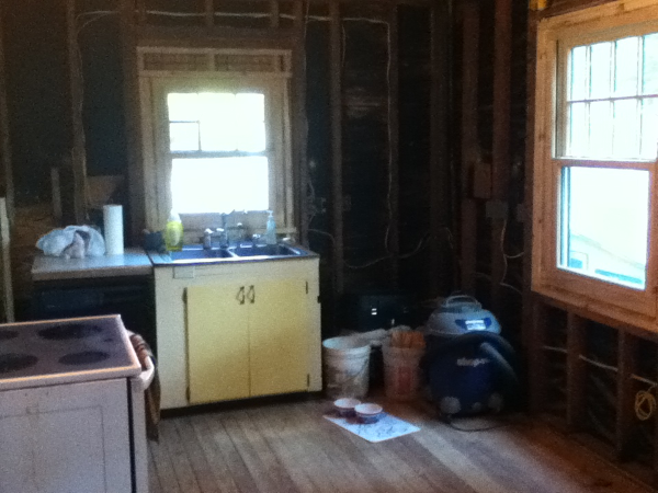 Kitchen demoed to bare studs, sink remains hooked up. New windows installed.